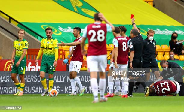 Josip Drmic of Norwich City is shown a red card by Match Referee, Kevin Friend as Erik Pieters of Burnley receives medical treatment during the...