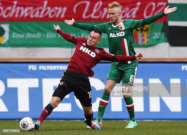 Josip Drmic of Nuernberg is challenged by Kevin Voigt of Augsburg during the Bundesliga match between FC Augsburg and 1 FC Nuernberg at SGL Arena on...