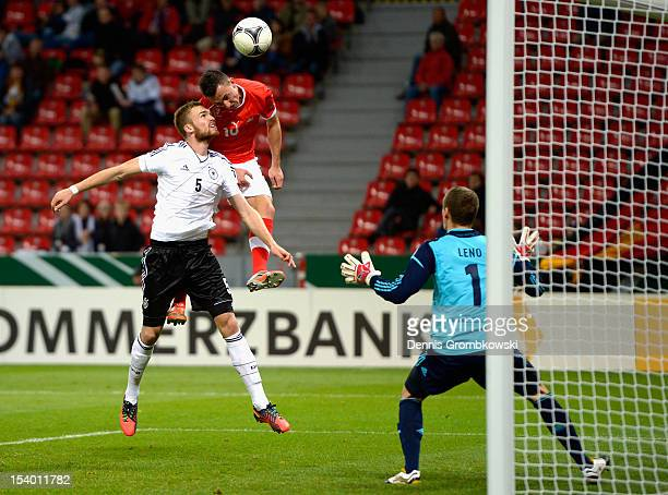 Josip Drmic of Switzerland scores his team's first goal under the pressure of Jan Kirchhoff of Germany during the Under 21 European Championship Play...