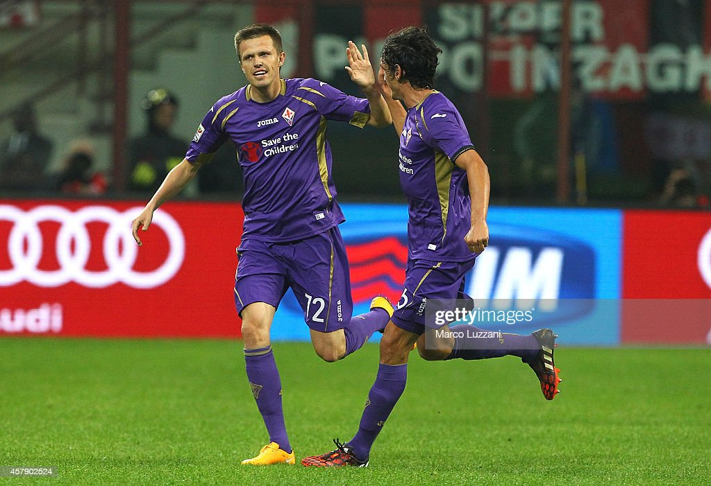 Josip Ilicic of ACF Fiorentina celebrates with his team-mate Stefan Savic after scoring his goal during the Serie A match between AC Milan and ACF Fiorentina at Stadio Giuseppe Meazza on October 26, 2014 in Milan, Italy.