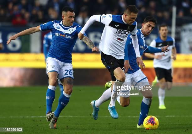 Josip Ilicic of Atalanta BC competes for the ball with Bruno Martella and Emanuele Ndoj of Brescia Calcio during the Serie A match between Brescia...