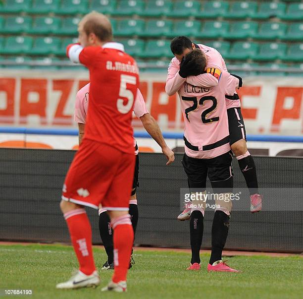 Josip Ilicic of Palermo celebrates the opening goal with team mate Fabrizio Miccolo as Andrea Masiello of Bari looks dejected during the Serie A...