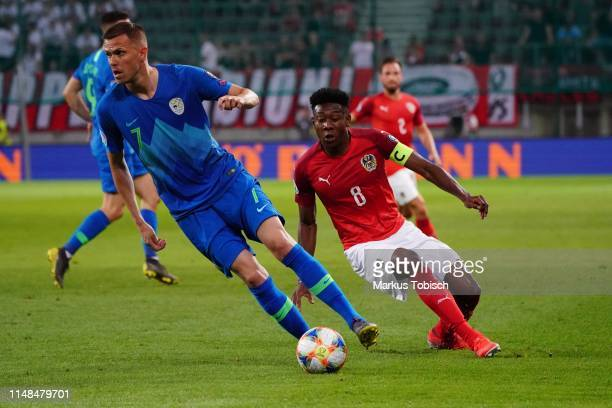 Josip Ilicic of Slovenia and David Alaba of Austria compete for the ball during the UEFA Euro 2020 Qualifier match between Austria and Slovenia at...