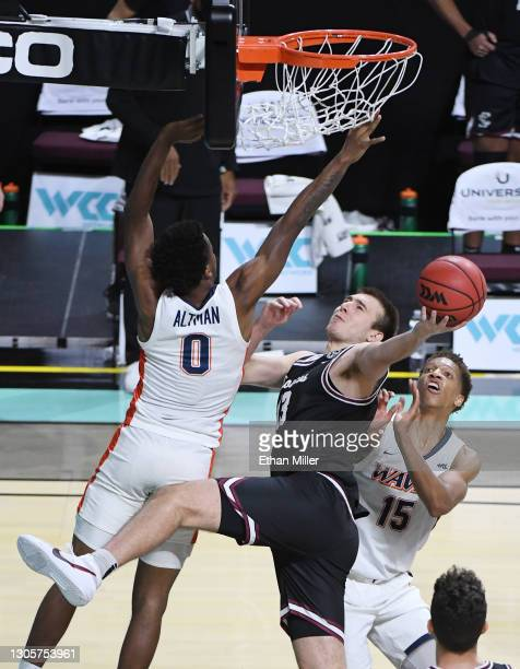 Josip Vrankic of the Santa Clara Broncos is fouled as he shoots against Sedrick Altman and Kessler Edwards of the Pepperdine Waves during the West...