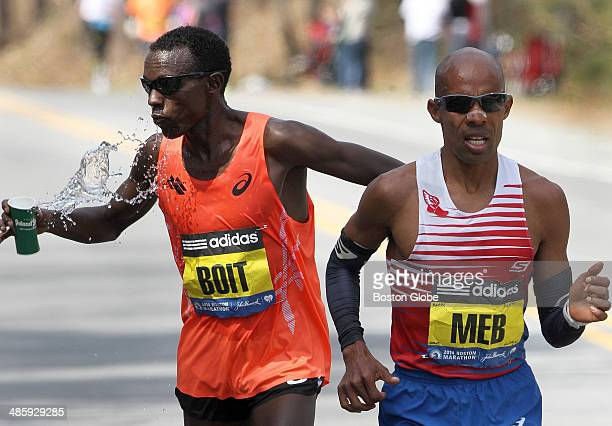 Josphat Boit, of the United States, takes water past Mile 12 in Wellesley as he shadowed Mebrahtom Keflezighi of the United States, for a good part...