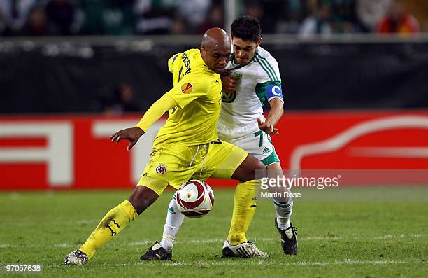 Josue of Wolfsburg and Marcos Senna of Villareal compete for the ball during the UEFA Europa League knock-out round, second leg match between VfL...