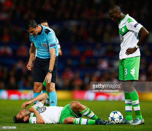 Josuha Guilavogui of VfL Wolfsburg and referee Viktor Kassai stand over an injured Christian Trasch of VfL Wolfsburg during the UEFA Champions League...