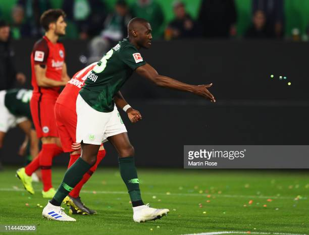 Josuha Guilavogui of VfL Wolfsburg removes small objects from the ground prior to the Bundesliga match between VfL Wolfsburg and Eintracht Frankfurt...