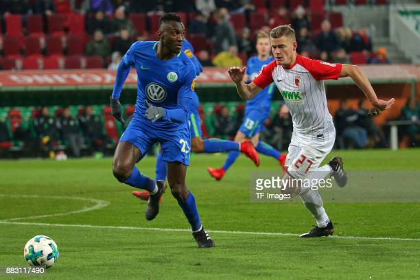Josuha Guilavogui of Wolfsburg and Alfred Finnbogason of Augsburg battle for the ball during the Bundesliga match between FC Augsburg and VfL...
