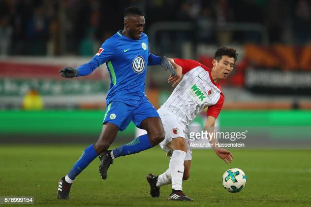 Josuha Guilavogui of Wolfsburg fights for the ball with Koo Jacheol of Augsburg during the Bundesliga match between FC Augsburg and VfL Wolfsburg at...
