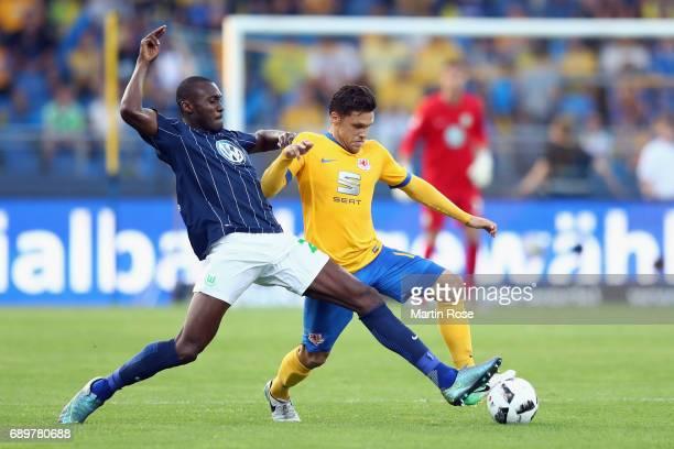 Josuha Guilavogui of Wolfsburg is challenged by Mirko Boland of Braunschweig during the Bundesliga Playoff leg 2 match between Eintracht Braunschweig...