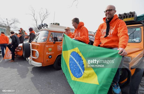 Jouko Juijin and Tyuren Hofstee hold a Brazilian flag as they join a caravan of 22 orange vehicles in New York's Battery Park before they begin a...