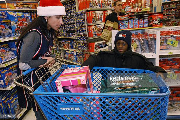 Joumana Kidd helps pick toys for this little boy as the New Jersey Nets and New Jersey Devils Wives treat several Newark New Jersey youngsters to a...