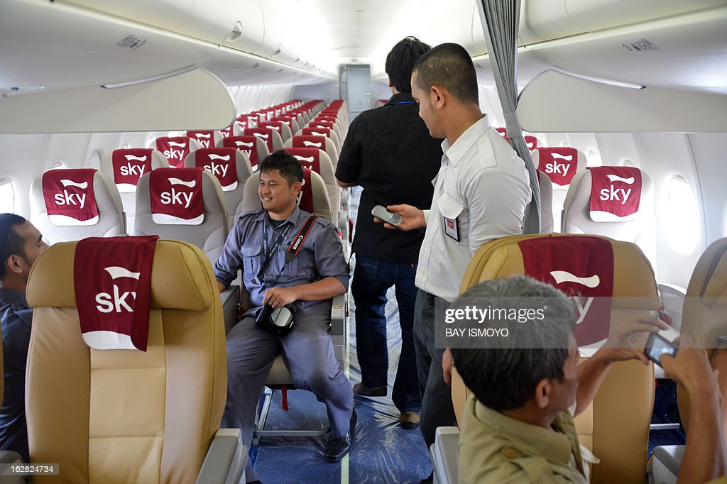 Jounalists and officials look around the cabin of Sky aviation's new aircraft, the Sukhoi Superjet 100, during a launching ceremony at Halim airport in Jakarta on February 28, 2013. Indonesia has certified Russian-made Sukhoi civilian jets as airworthy, allowing the export of the planes to the booming aviation market despite a pending probe into a crash that killed all 45 onboard. AFP PHOTO / Bay ISMOYO