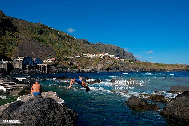 A joung man jumping into the natural rock pools in the coast of the town of Garachico in rhe northern part of the Canary island of Tenerife Spain