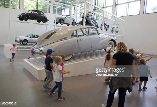 Joung visitors and old cars in the Museum Pinakothek der Moderne in Munich Hans Ledwinka carr Tatra 87 from 1937 In the background VW Beetle Typ 11...