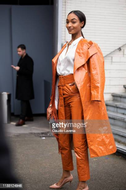 Jourdan Dunn wearing a white shirt orange long leather jacket with matching pants nude heels and black bag is seen outside Balmain on Day 5 Paris...