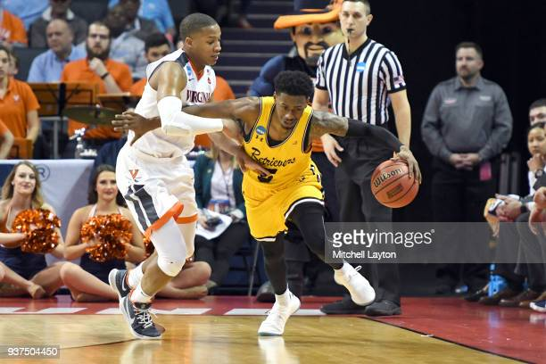 Jourdan Grant of the UMBC Retrievers dribbles by Devon Hall of the Virginia Cavaliers during the first round of the 2018 NCAA Men's Basketball...