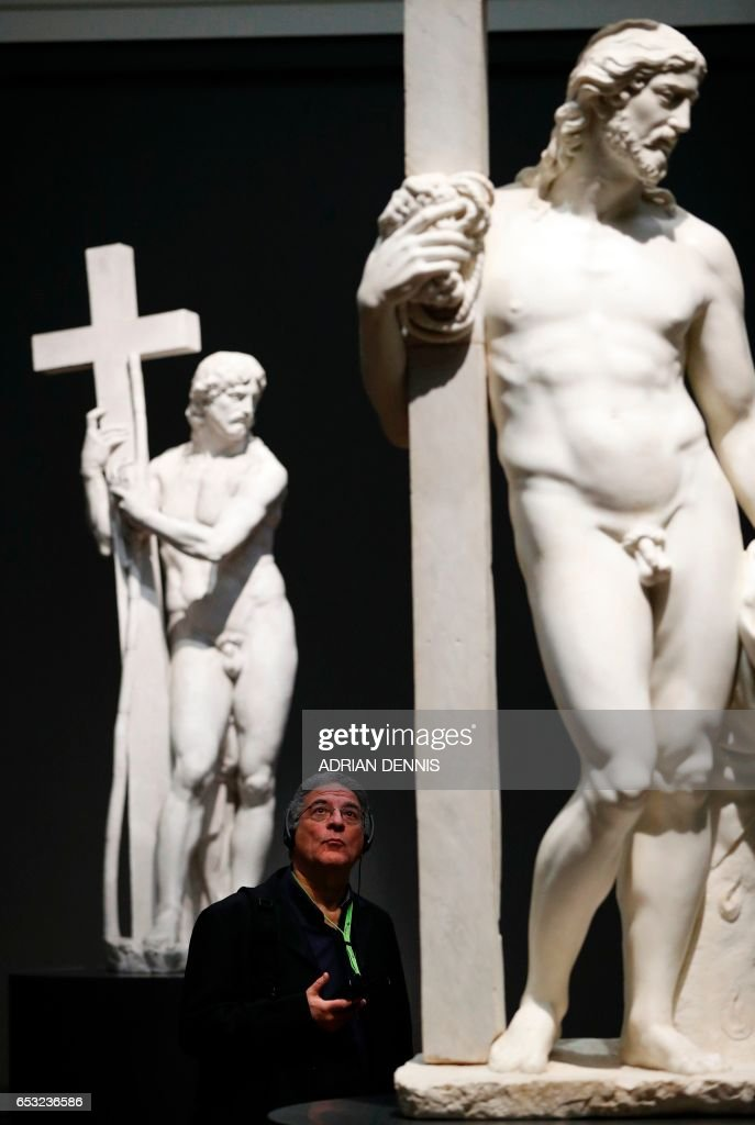 A journalist admires a painting (C) entitled 'Christ carrying the Cross', by Sebastiano del Piombo, during a press preview to promote the forthcoming exhibition, 'Michelangelo and Sebastiano', at The National Gallery in London on March 14, 2017. The exhibition, set to open on 15 March and run until 25 June 2017, will be devoted to the creative partnership between Michelangelo (1475-1564) and Sebastiano (1485-1547), featuring some loaned pieces which have not left their collections for centuries. /