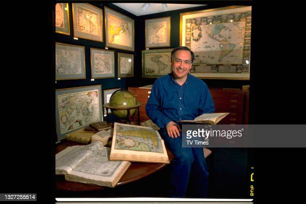 Journalist Alastair Stewart, best known for hosting ITV News, photographed in an antique shop, circa 1990.