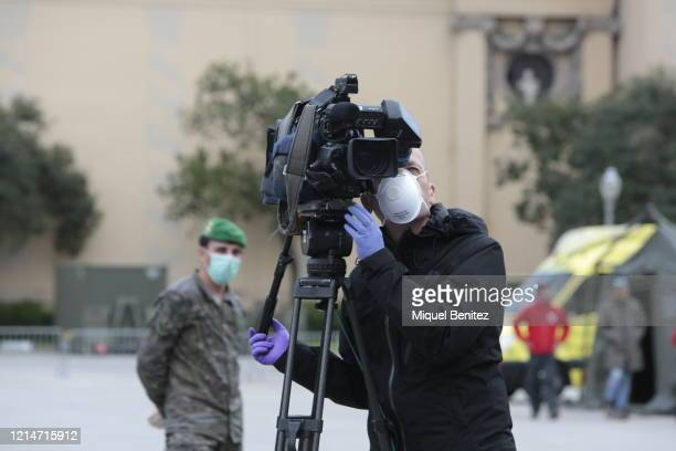 A journalist and a Spanish soldier wear face mask during the press conference at the pavilion at Fira de Barcelona as final preparations are made...