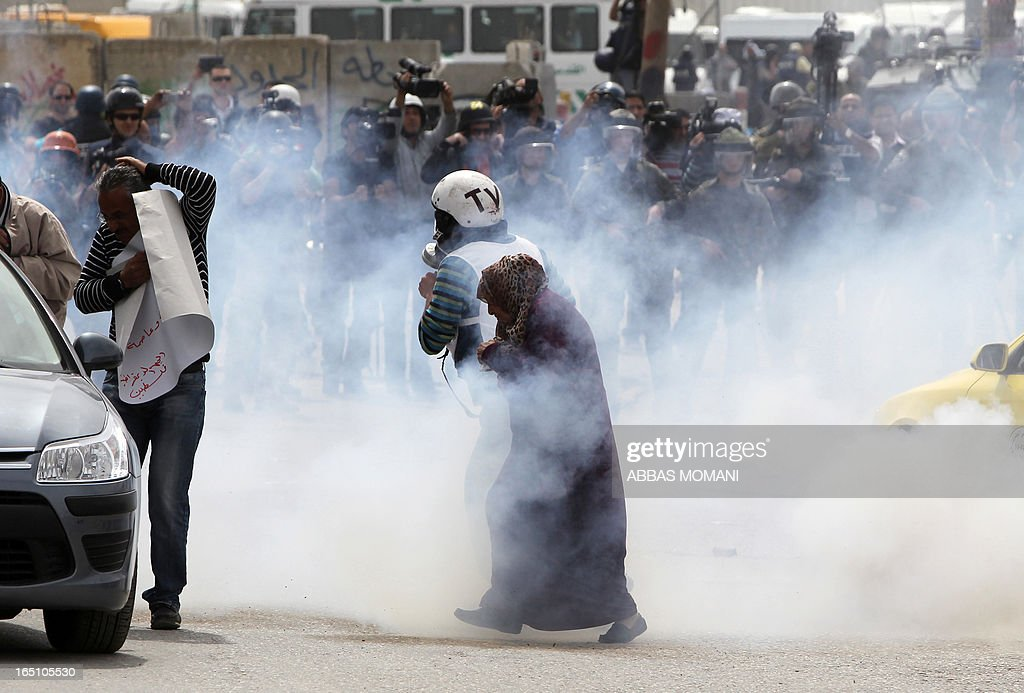 A journalist and an elderly woman walk away from tear gas smoke during clashes between Palestinians protesters and Israeli soldiers following a rally commemorating the 37th anniversary of 'Land Day', on March 30, 2013 near the Qalandia checkpoint in the Israeli occupied West Bank. Nearly 200 Palestinians clashed with Israeli forces in Qalandia, who responded with tear gas.
