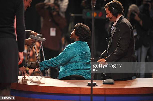PBS journalist and debate moderator Gwen Ifill is helped onto the stage before the vice presidential debate at the Field House of Washington...