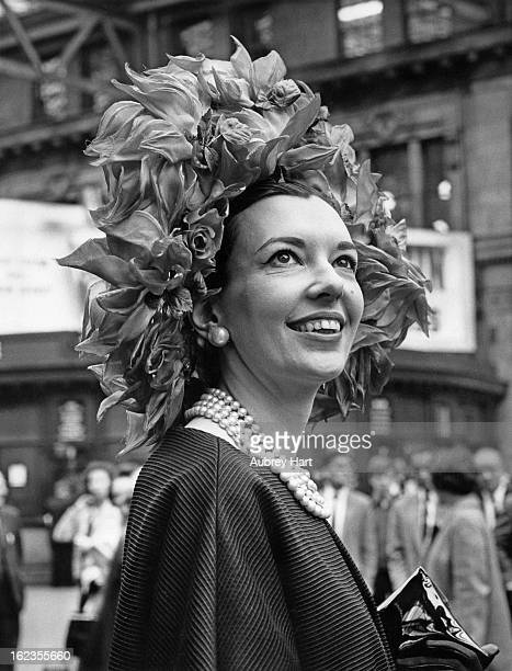 Journalist and novelist Una-Mary Parker, the wife of Archie Parker of Knightsbridge, wears a black silk coat and a hat decorated with red silk rose...