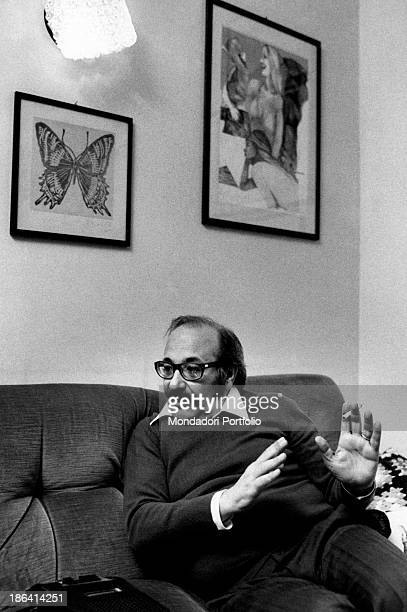 Journalist and writer Antonio Perria talks with a cigarette in his hand sitting on a sofa in the living room of his home being interviewed about his...