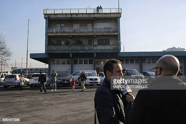 A journalist conducts an interview as people look at the site where suspected Berlin truck attacker Anis Amri was killed in Milan on December 23 2016...