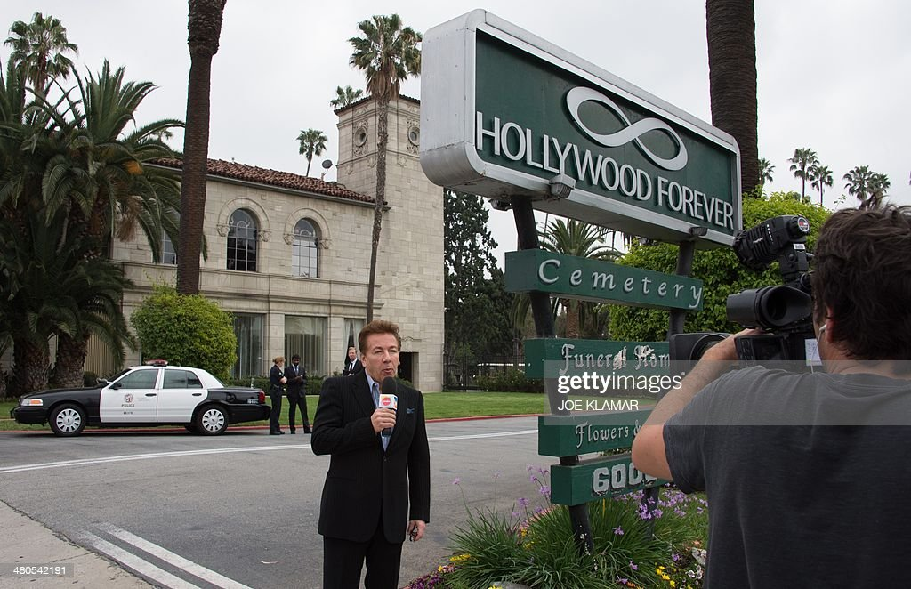 A TV journalist delivers his report on the funeral of Mick Jagger's late girlfriend LWren Scott outside Hollywood Forever Cemetery in Hollywood, California on March 25, 2014. The model-turned-fashion designer was found hanged in her luxury New York apartment last week. She was 49. The cemetery was closed for the roughly one-hour service, held amid tight security.
