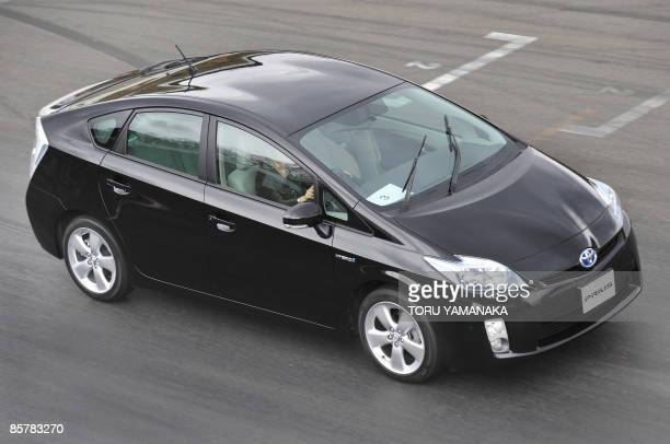 A journalist drives a prototype of Toyota's new hybrid vehicle Prius during a test drive event at Fuji Speedway in Oyama 100km west of Tokyo on March...