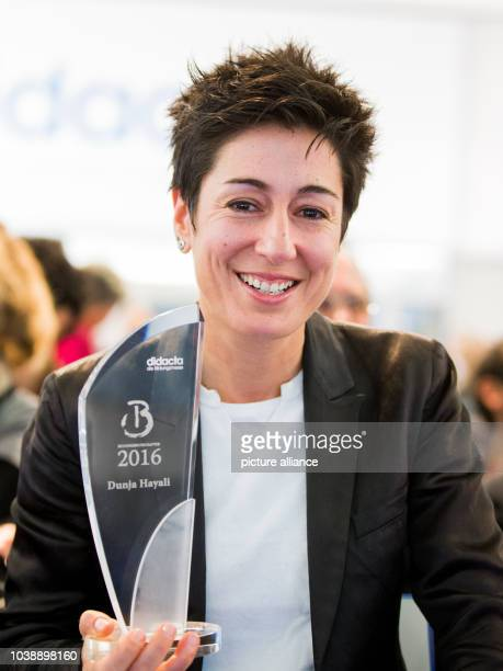 Journalist Dunja Hayali smiles as she holds her award in her hands during the education trade fair 'Didacta' in Cologne Germany 17 February 2016...