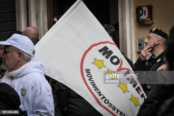 Journalist Enrico Lucci arrives with a flag of Italy's populist Five Star Movement during Democratic Party meeting in Rome Monday March 12 2018...