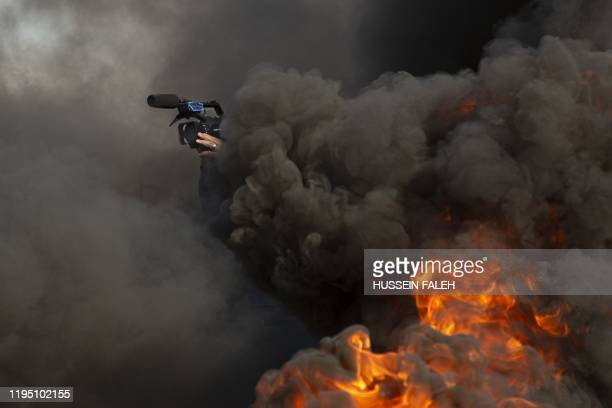 A journalist films amid burning tires ignited by antigovernment protesters during a demonstration in the southern Iraqi city of Basra on January 21...
