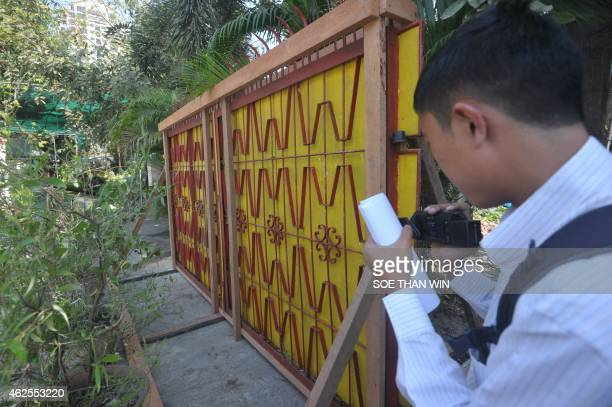 A journalist films an old gate of the Chairman of National League for Democracy Aung San Suu Kyi's residence in Yangon on January 31 2015 A set of...