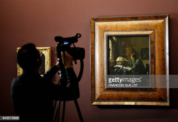 A journalist films 'The Astronomer' an oil on canvas by late Dutch painter Johannes Vermeer during the press visit of an exhibition entitled 'Vermeer...