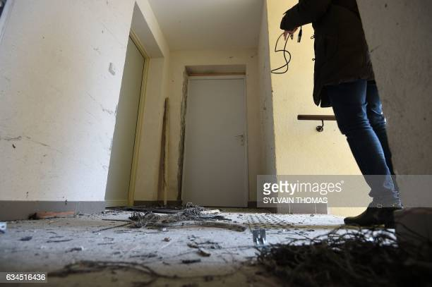 A journalist films the debris of an explosion after French antiterrorist police raided an apartment where suspects believed to be involved in...