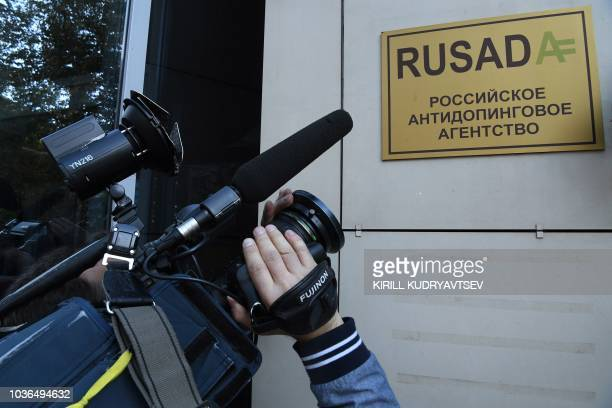 A journalist films the sign on the RUSADA building in Moscow on September 20 2018 The World AntiDoping Agency on September 20 2018 lifted a ban on...