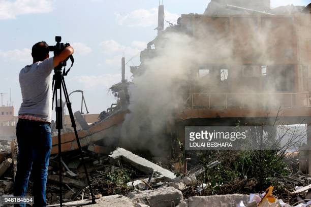 TOPSHOT A journalist films the wreckage of a building described as part of the Scientific Studies and Research Centre compound in the Barzeh district...