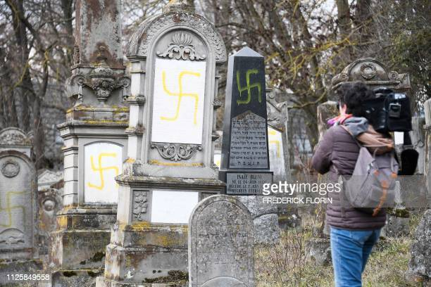 A journalist films with a camera graves vandalised with swastikas at the Jewish cemetery in Quatzenheim on February 19 on the day of a nationwide...