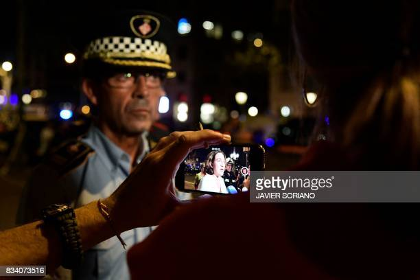 A journalist films with his smartphone as Barcelona's Mayor Ada Colau speaks to the press on the Rambla boulevard after a van ploughed into the crowd...