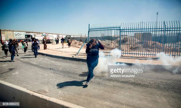 TOPSHOT A journalist flees from teargas while covering clashes after a demonstration against the US decision to recognise Jerusalem as the capital of...