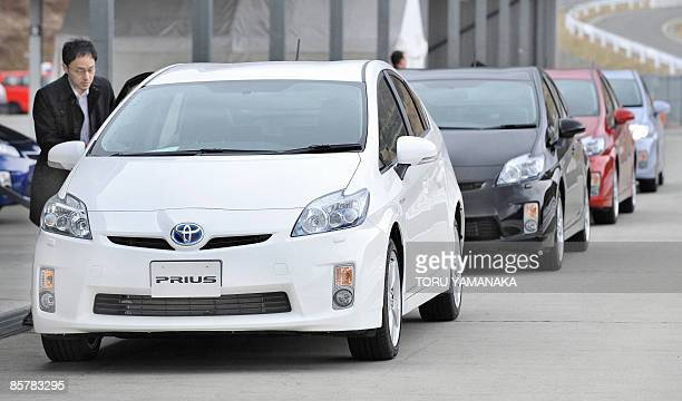 A journalist gets on a prototype of Toyota's new hybrid vehicle Prius during a test drive event at Fuji Speedway in Oyama 100km west of Tokyo on...