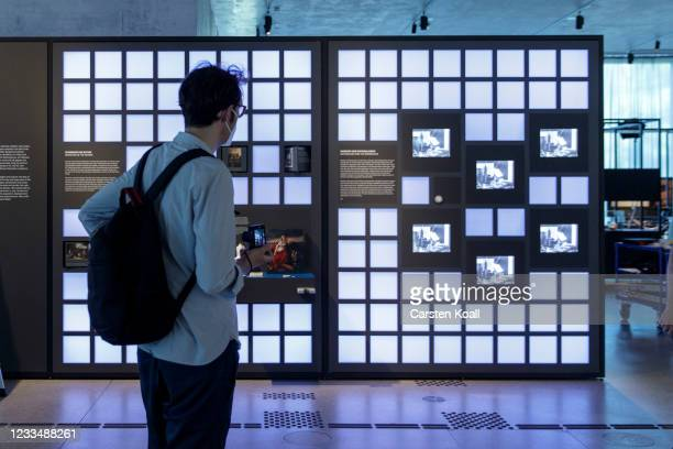 """Journalist goes to an exhibit wall in the """"Nation and Nationalism"""" sectionin the new Documentation Center for Displacement, Expulsion and..."""