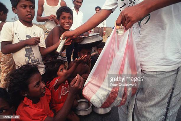 A journalist hands out small parcels of food to children who have survived one of the biggest cyclones to hit Bangladesh in recent decades The...
