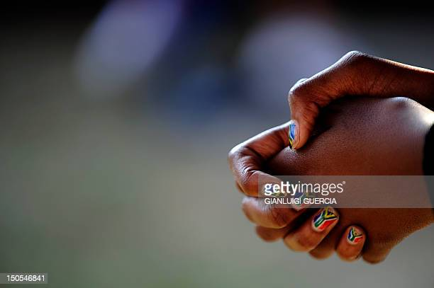A journalist has her nails painted with the colours of the South African flag as she attend a Football for hope Painting workshop on June 30 2010 at...