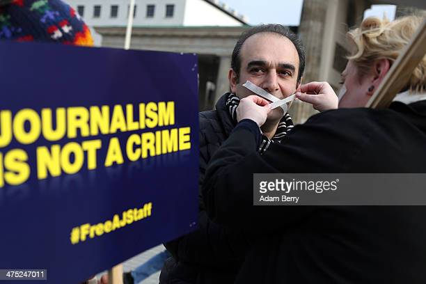 A journalist has his moth taped shut during a protest in front of the Brandenburg Gate against the detaining of Al Jazeera reporters currently in...