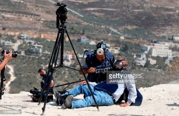 Journalist helps a colleague after being hurt during clashes between Palestinian protesters and Israeli forces, following a demonstration in Asira...