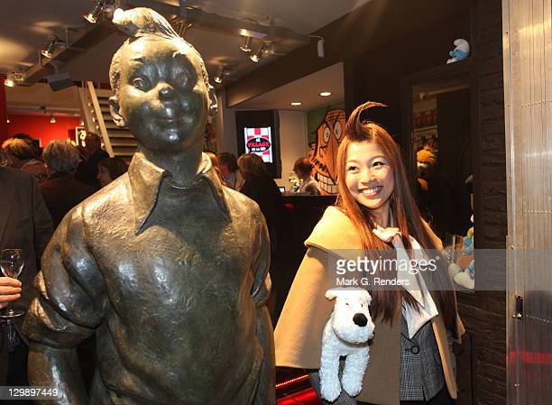 A journalist holding a cuddly toy of comic hero Tintin's dog Snowy admires the sculpture of Tintin by sculptor Nat Neujean during its inauguration at...